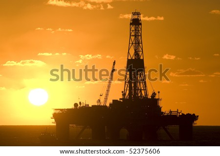 oil drilling rig in offshore area during sunset time