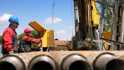 Oil drilling rig workers lifting drill pipe. Oil and Gas Industry. Drilling Rig. Oil and Gas Worker.