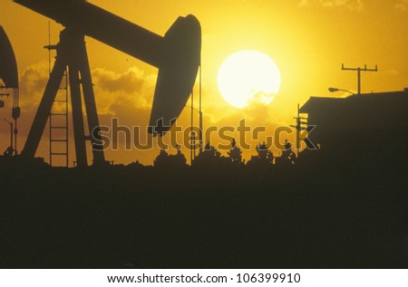 Oil drilling well silhouetted at sunset