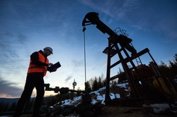 Oil engineer in work vest at oil pump rocker-machine, making notes while checking work of balanced beam petroleum pump jack under beautiful evening sky. Concept of oil extraction, petroleum industry.