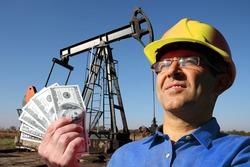 Oil engineer with yellow hard hat holding US dollar bills in front of oil well. Money, salary, oil jobs concept
