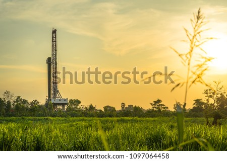 Oil field, Onshore drilling rig around with agriculture field. View from the another site of sugar crane field while the sunset time.
