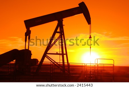 Oil field pump jack with a setting sun behind it