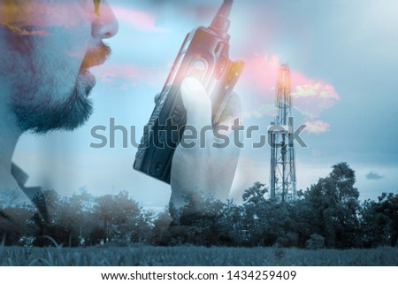 Oil field supervisor is using radio to command the operation, with background of drilling site. Working in drilling and petroleum operation concept with double exposure photo merge, background.