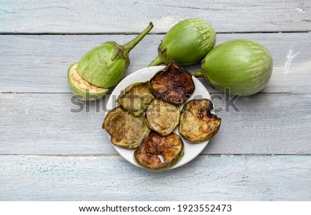 Oil Fried Eggplant or Brinjal in a Plate with Raw Eggplant on White Wooden Background with Selective Focus, Also Known as Begun Bhaja Zdjęcia stock ©
