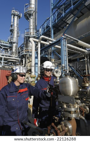 oil, gas and engineers, surrounded by pipelines inside oil refinery