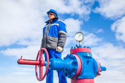 Oil, gas industry. The mechanic - the repairman, gas production operator opens the valve, gas equipment and fitting at the well