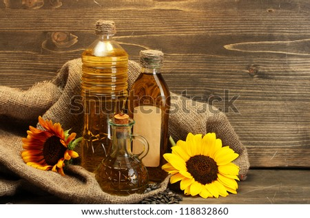oil in bottles, sunflowers and seeds, on wooden background