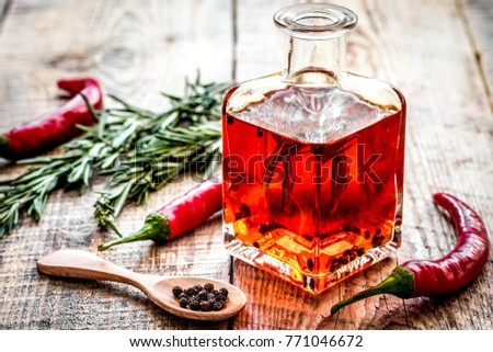 oil in carafe with spices and chili on wooden background