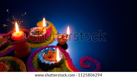 Oil lamps lit on colorful rangoli during diwali celebration #1125806294