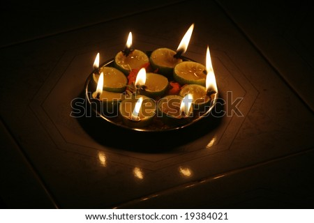 Oil lamps sit on a tray at a temple.