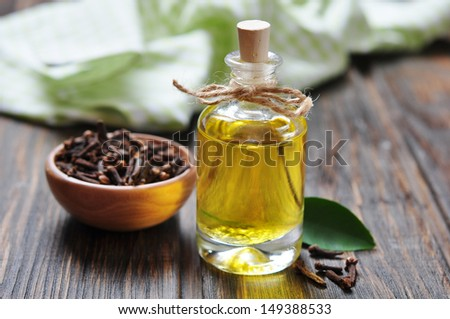 Oil of cloves in a glass bottle over wooden background