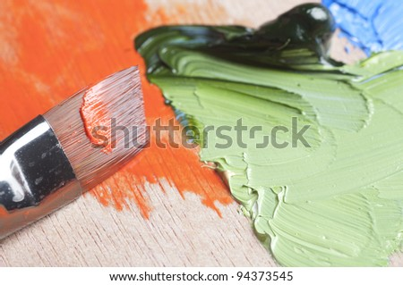 Oil Paints and brush on wooden palette - stock photo
