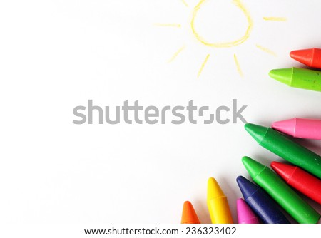 Oil pastel crayons lying on a paper with painted children\'s drawing. Copy space background. Selective focus