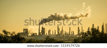 Oil petroleum refinery pollution smoke stack pouring carbon smog into the atmosphere climate change and global warming #1159579726