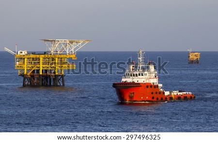 Oil platform and a supply vessel at sunset