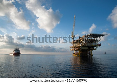 oil platform at sea with offshore vessel nearby during morning #1177450990