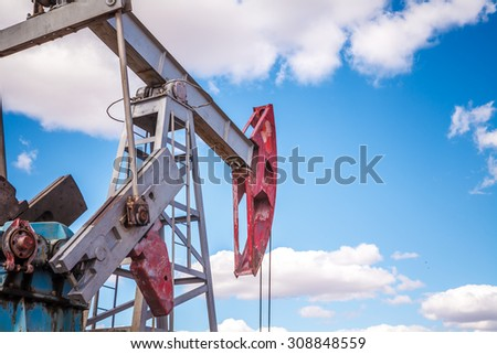Oil pump in the field on a background cloudy sky #308848559