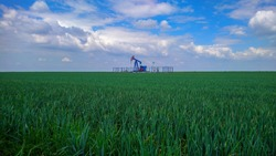 Oil pump in the wheat field against blue sky. Nature and technology contrast