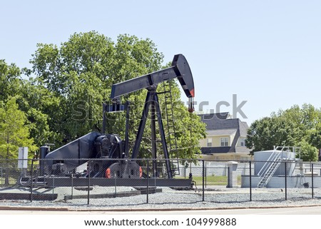 Oil Pump Jack at the Residential Area at the Middle of the Street.