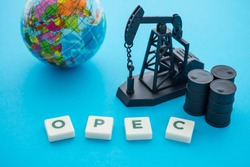 Oil pump jack, barrels, world globe ball and word OPEC Organization of the Petroleum Exporting Countries on blue background. Concept of crude oil production, petroleum industry or petrodollar.