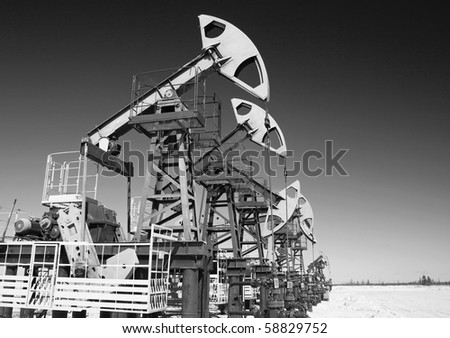 Oil pump jack on a sand. Black and white photo