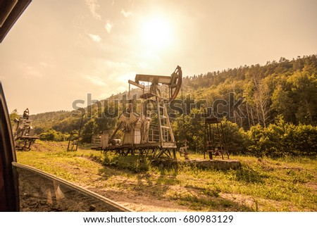 oil pump near a forest, visible from the window of a passing car