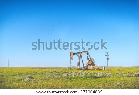 Oil Pump Oil Rig Energy in countryside with blue sky background.
