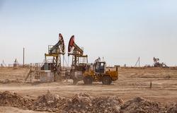 Oil pumping jacks on oil field in desert clay ground. Bulldozer making groundworks. Zhanaozen, Kazakhstan.