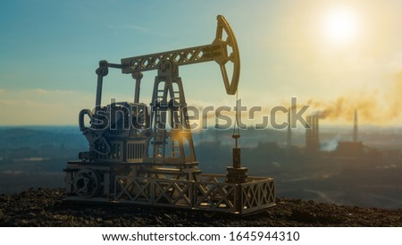 Oil pumping pump tower on the background of smoking plants. Natural resource extraction, fuel