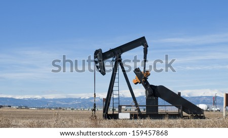 Oil pumpjack against snowy mountains in Colorado.