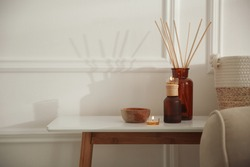 Oil reed diffuser and candles on wooden table near white wall, space for text. Interior decor