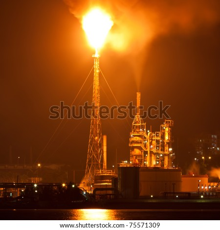 Oil refinery at night creating a huge smoke cloud with reflections on the nearby ocean