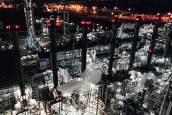 Oil refinery at night lit. Construction of an oil industrial facility. night lighting