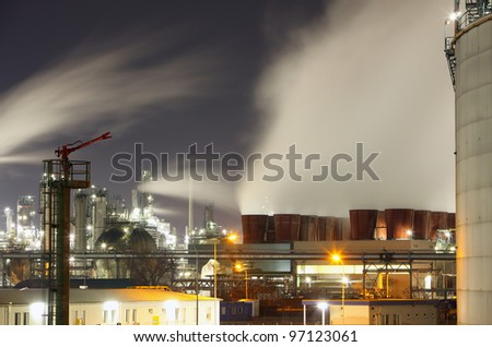 Oil refinery at night with steam/smoke flowing into the sky