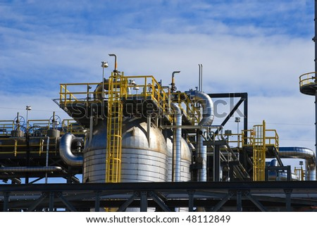 Oil refinery detail picture, against blue and partly cloudy sky.