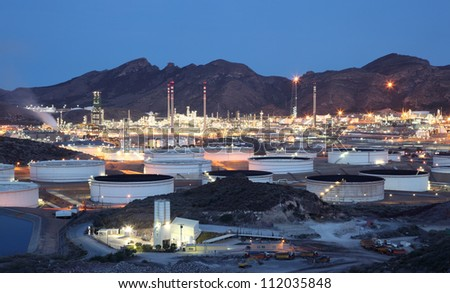 Oil refinery facilities illuminated at dusk