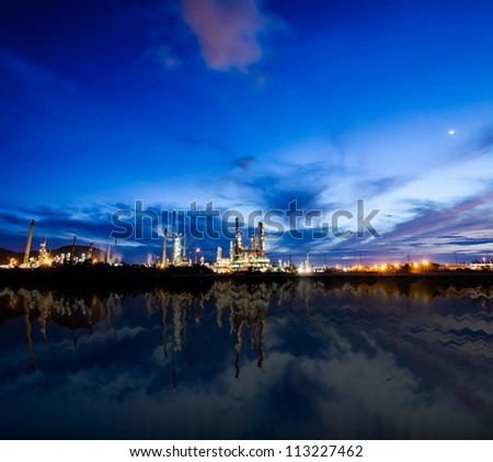 Oil refinery plant at twilight dark blue sky near river.