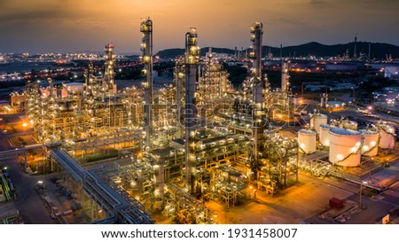 Oil refinery plant from industry zone, Aerial view oil and gas petrochemical industrial, Refinery factory oil storage tank and pipeline steel at night, Ecosystem and healthy environment.