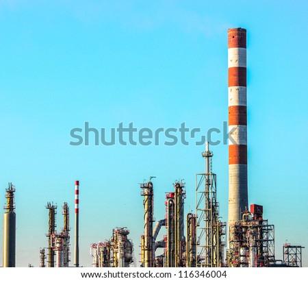 Oil refinery plant scene against blue sky