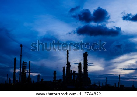 Oil refinery plant silhouette at twilight dark blue sky.