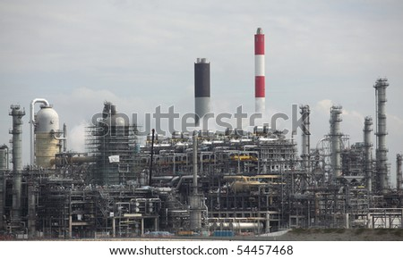 Oil refinery plant with it\'s stainless steel cylinders, it\'s valves, chimneys, pipes, tubes and construction and visible air-emission.