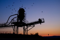 Oil refinery pump, sunset or sunrise,with a flock of birds flying away,copy space in the sky,Corona virus COVID-19 global pandemic crisis causing worldwide economic crash and oil stock market plummet