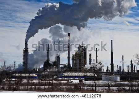 Oil refinery, smoke and smog pouring out of smoke stacks, against blue sky.