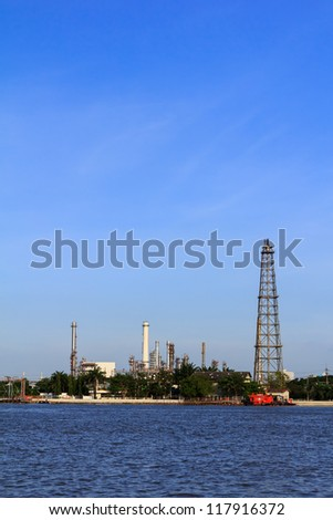 Oil refinery with chimney and blue sky