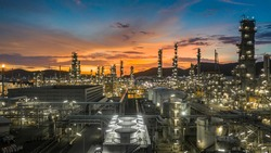 Oil refinery with oil storage tank and petrochemical plant industrial background at twilight, Aerial view oil and gas refinery at twilight.
