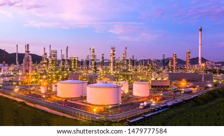 Oil​ refinery​ with oil storage tank and petrochemical​ plant industrial background at twilight, Aerial view oil and gas refinery at twilight.