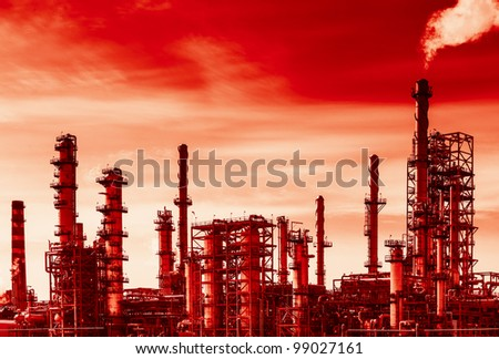 Oil refinery with smoke from the pipe. Black and white photography with red tint to show danger and global warming.