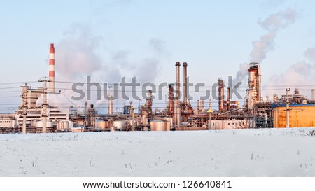 oil refinery with smoking chimneys in winter against blue sky