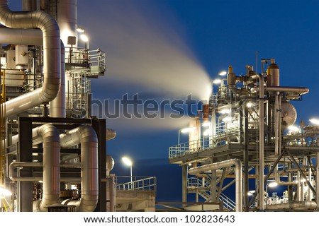 Oil refinery with water vapor in Hamburg, Germany, petrochemical industry night scene